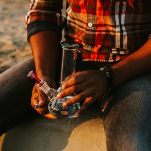 man holding a glass bong and red bowl